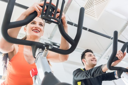 Low angle view of a smiling woman doing workout at fitness gym Stock Photo
