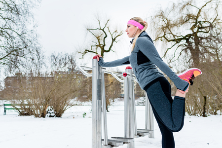 Woman stretching her legs for sport on a winter day in snow city Stock Photo