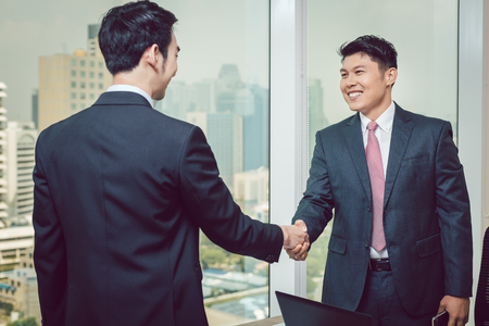 Businessmen shaking hands with each other in the office