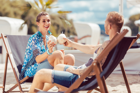 Young couple sitting on chair at beach toasting coconut water