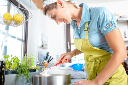 Smiling mid-adult woman preparing cake in kitchen Stock Photo