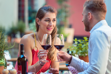 Portrait of a happy couple toasting glass of red wine Stock Photo