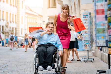Woman and man in wheelchair with shopping bags in town