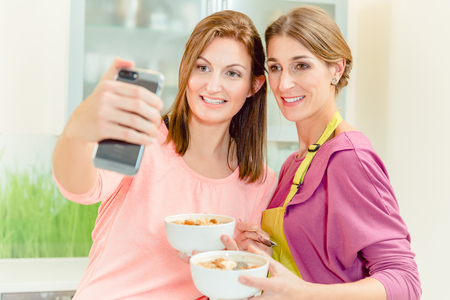 Two smiling young female friends holding bowl of oatmeal taking selfie on smart phone