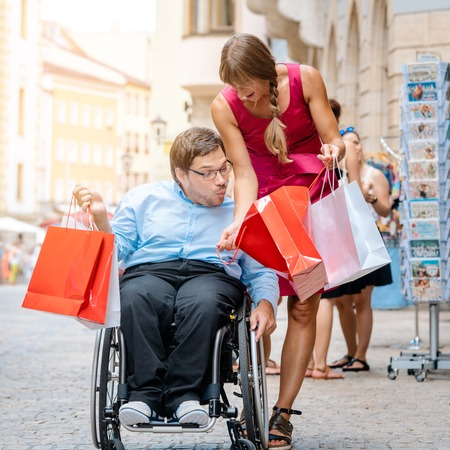 Handicapped man and his friend shopping in town showing each other what they have bought