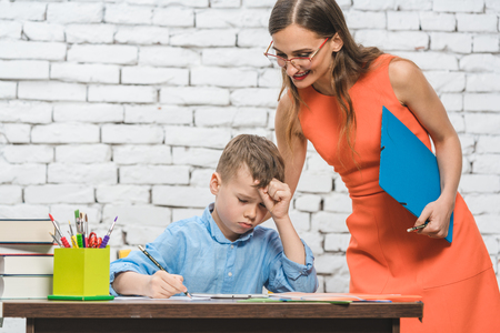 Student boy doing difficult work in school supervised by his teacher