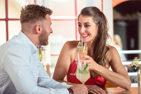 Portrait of happy young couple drinking cocktails