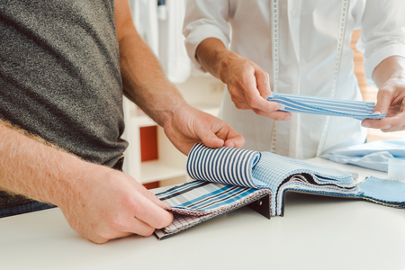 Tailor and customer choosing material for bespoke shirt from pattern book Stock Photo