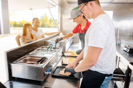 Young chefs in a food truck preparing Mexican food for their waiting customers Banque d'images - 115417456