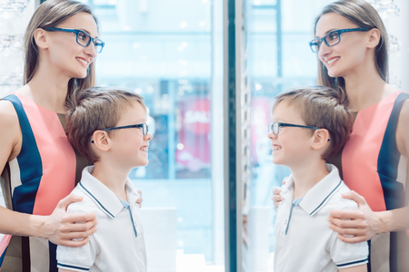 Mother and her son testing new glasses in the mirror in optometrist store