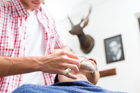 Close-up of barbers hand shaving mans beard with straight razor