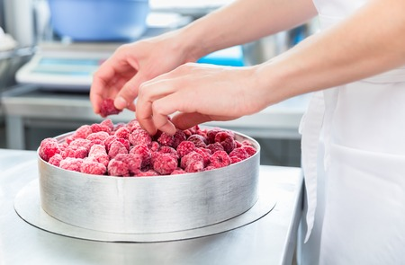 Woman confectioner making raspberry cake in bakery Stock Photo