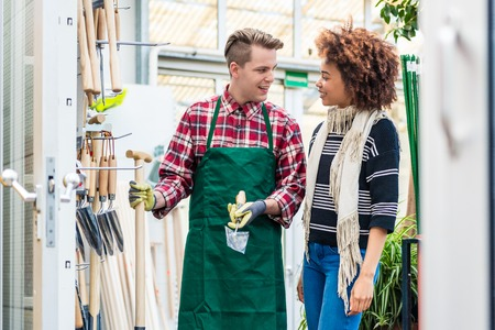 Handsome and cheerful worker wearing a green apron while helping a customer with choosing a gardening tool in a modern flower shop