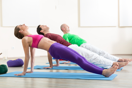 Healthy people doing stretching exercising in yoga class