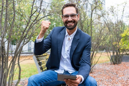Smiling successful businessman holding digital tablet clenching his fist in the park