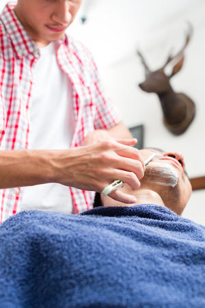 Young man getting an old-fashioned shave with straight razor Stock Photo