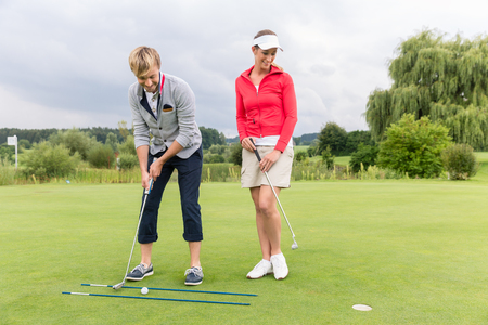 Woman looking at male golfer putting ball in green