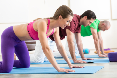Young woman practicing yoga pose with two men on exercise mat Stock Photo