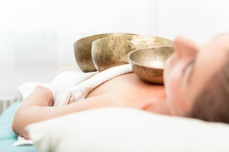 Woman relaxing in spa receiving singing bowl therapy on her body Stock Photo