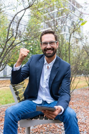 Portrait of successful businessman sitting on park bench holding digital tablet clenching his fist Stock Photo
