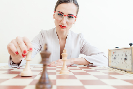 Businesswoman making strategic move in game of chess