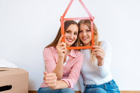 Two women having rented a new apartment moving in looking thru folding rule
