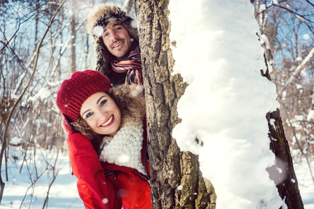 Playful couple hiding behind a tree trunk in the snow looking into the camera