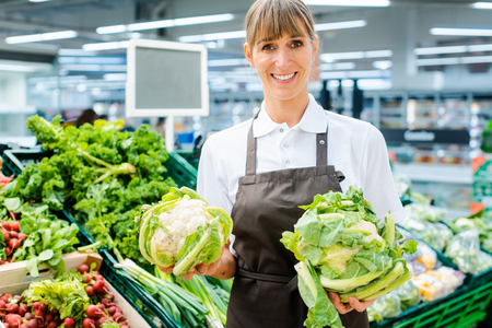 Shop assistant woman in supermarket showing the fresh produce with pride looking into camera