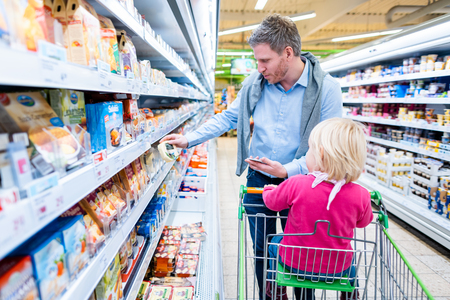 Man with his child in fresh department of supermarket looking for dairy products