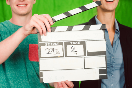 Assistant holds movie slate into the camera to start the production of a video piece Stock Photo