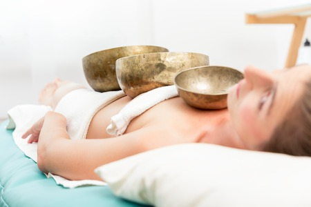 Young woman lying on bed in spa receiving sound therapy with singing bowl on her body Stock Photo