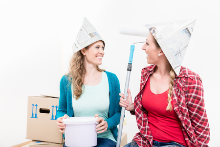 Smiling female friends wearing paper hat holding paint bucket and roller against white background Stock Photo