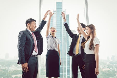 Group of smiling businesspeople standing near the window raising their hands Stock Photo