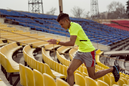 Close-up of a man running on stadium staircase