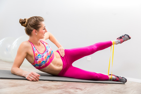 Healthy young woman doing exercise with yellow resistance band in the gym