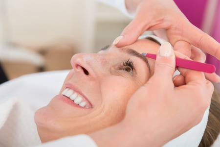 Smiling beautiful woman gets eyebrow correction procedure in salon