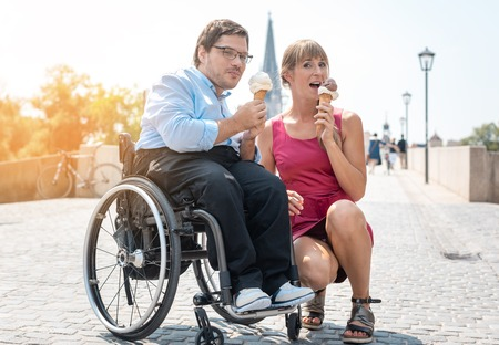 Disabled man and his friend having ice cream in town during a city excursion
