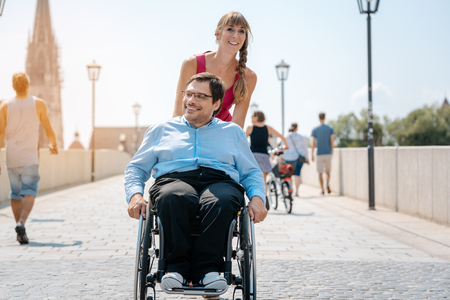 Woman and her friend in a wheelchair having stroll through the town enjoying the sun