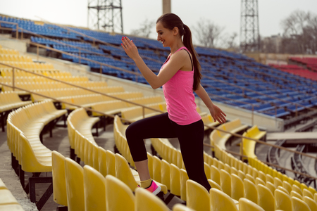 Smiling happy woman exercising on stadium staircase