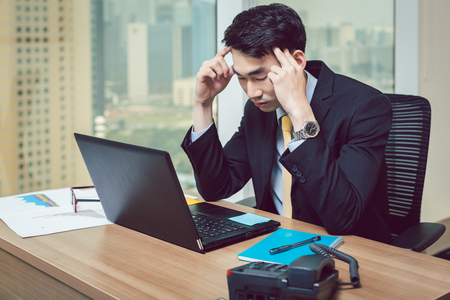 Worried young businessman having headache at workplace