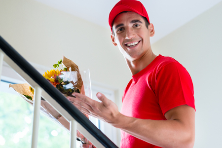Smiling delivery man in red cap and t-shirt holding flower bouquet