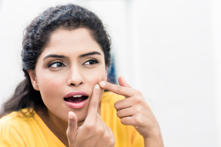 Young woman looking in mirror squeezing pimple