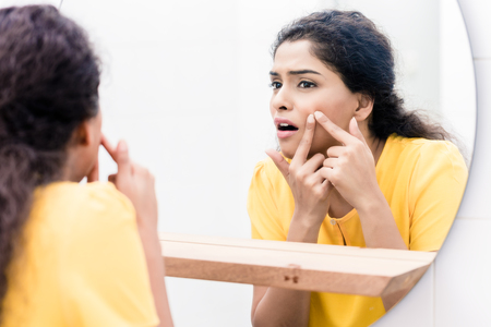 Close-up of a woman looking in mirror squeezing pimple Imagens