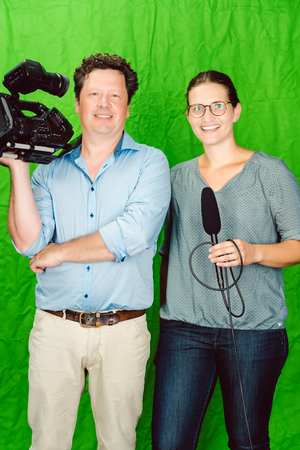 Crew of reporter and cameraman posing in the studio looking into the camera
