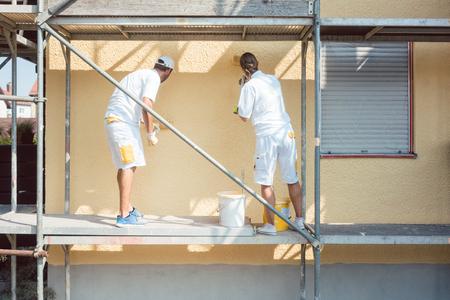 Vue arrière de l'homme et de la femme peintre travaillant à colorier le mur jaune