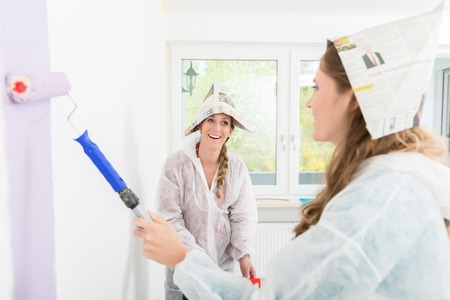 Smiling woman looking at her friend painting the wall with anchor roller Imagens