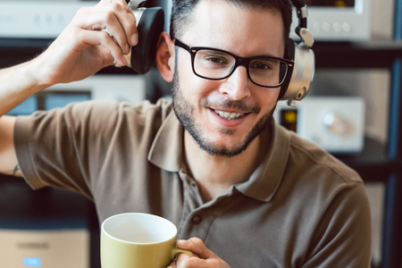 Man drinking coffee and listening to music being carried away by the sound