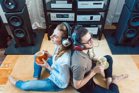 Couple with headphones enjoying music from the Hi-Fi stereo leaning at each other