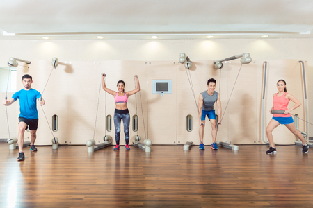 Portrait of a determined fit young man exercising with the resistance bands of an anchor gym system mounted on wall in a trendy fitness club Imagens