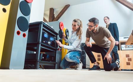 Junges Paar, Frau und Mann, kaufen High-End-Stereogeräte im Laden